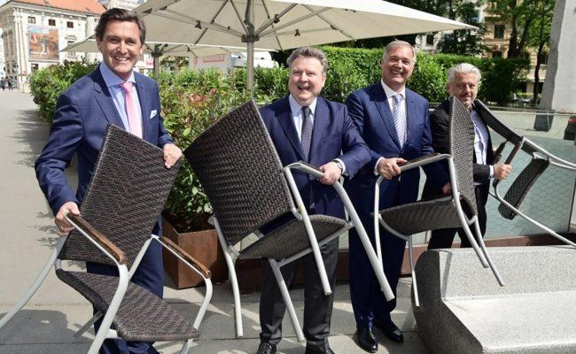 Peter Hanke, Michael Ludwig, Walter Ruck und Hans Arsenovic tragen Stühle eines geschlossenen Lokals