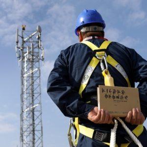"""Techniker hält Ausgabe der """"The Huawei Story"""" (chinesische Version) vor einem 5G Sendemast"""